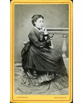 Femme en robe et manteau posant assise