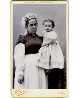 Nourrice en coiffe avec enfant en robe dans les bras