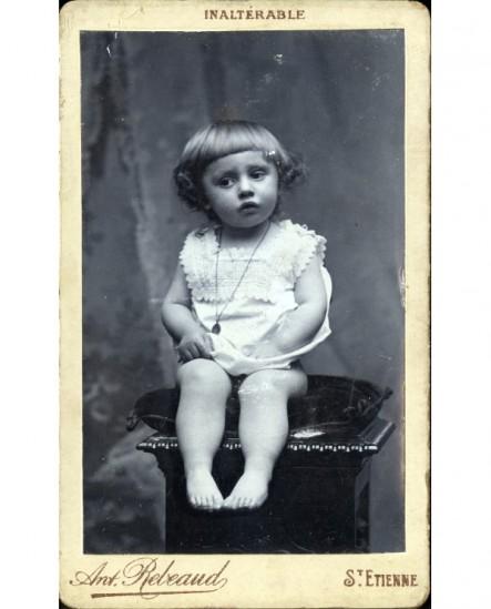 Enfant en chemise assis sur un coussin