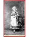 Femme debout en tenue Lorraine, quenouille de fils sur le bras