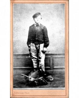 Jeune ouvrier en casquette tenant deux outils (broche et marteau)