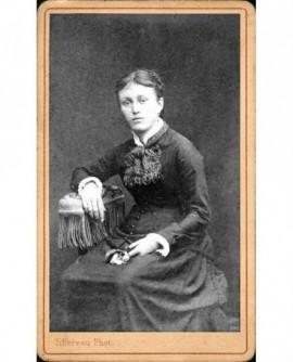 Femme assise une fleur à la main