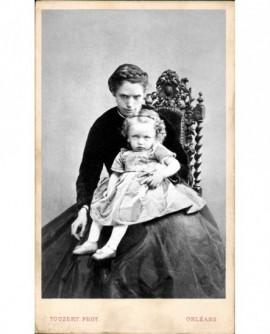 Jeune femme assise, un enfant sur ses genoux