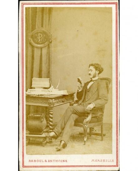 Homme assis à un bureau encombré, lisant un petit livre