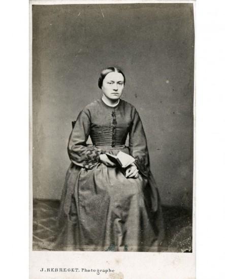 Femme assise tenant un livre