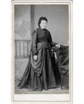 Femme en robe et bonnet debout, accoudée à un fauteuil