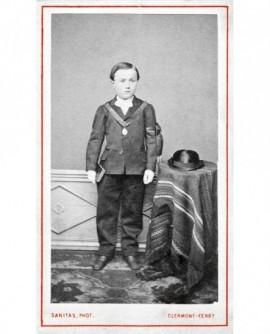 Jeune garçon debout, livre à la main, chapeau sur une table