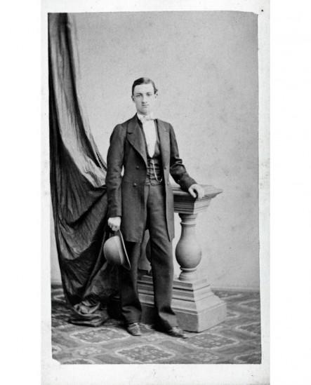 Jeune homme appuyé à une balustrade, chapeau en main