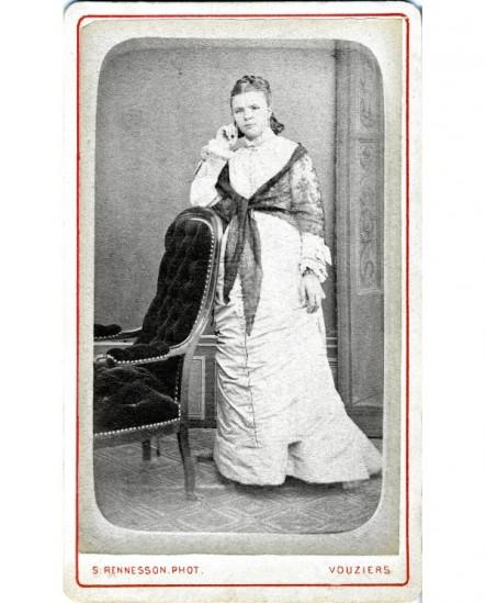 Femme en robe blanche et fichu noir accoudée à un fauteuil