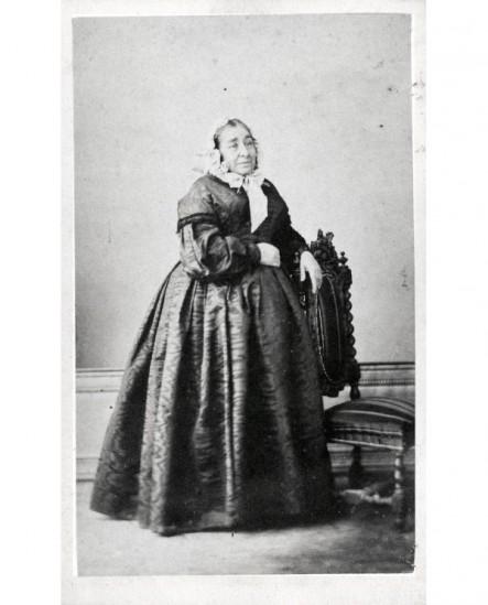 Femme âgée en coiffe appuyée sur une chaise