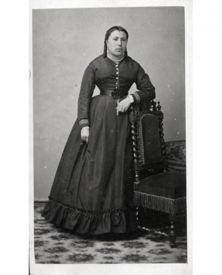 Femme aux couettes accoudée à une chaise