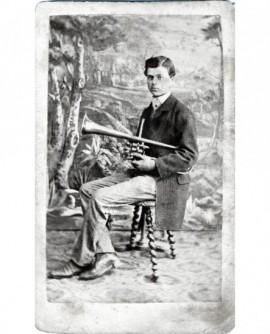 Jeune homme en habit assis avec un trombone