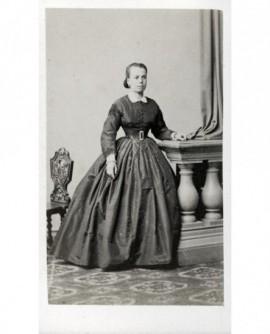 Jeune femme en robe à panier accoudée à une balustre