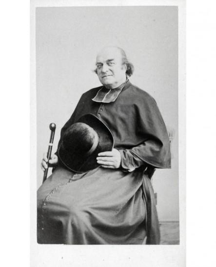 Ecclésiastique chauve assis avec chapeau et canne