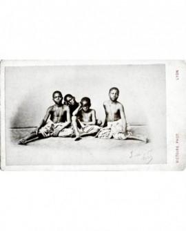Groupe de quatre enfants africains assis, torse nu