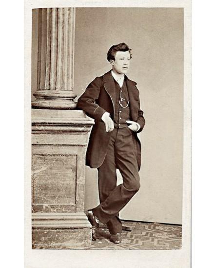 Jeune homme debout, pieds croisés, accoudé à une colonne