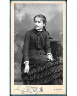 Jeune fille nattée en robe à volants assise, rose à la main