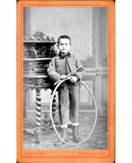 Garçon debout contre meuble avec cerceau et baguette (jouet)