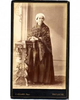 Femme en coiffe appuyée sur console avec châle
