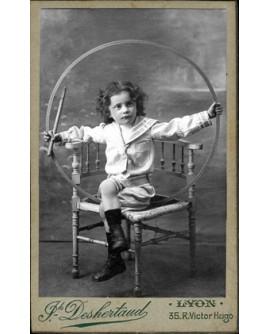 Jeune garçon assis, encadré par son cerceau, tenu avec la baguette