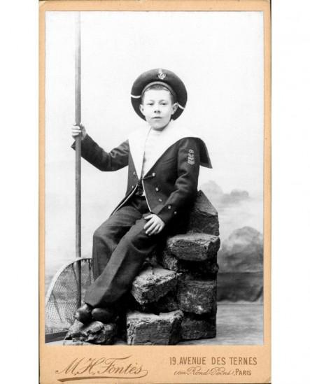 Jeune garçon en costume marin tenant un filet à crevettes