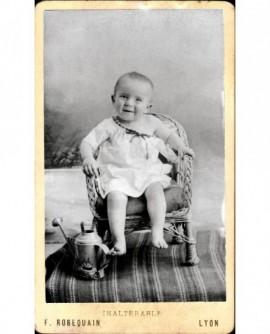 Bébé en chemise épaule dénudée, assis sur fauteuil en osier