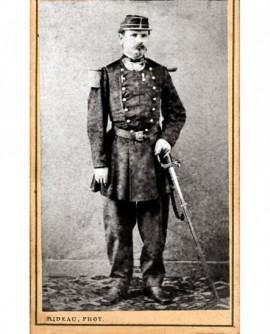 Militaire à impériale (marsouin) en képi appuyé sur son sabre. M. Bonnami