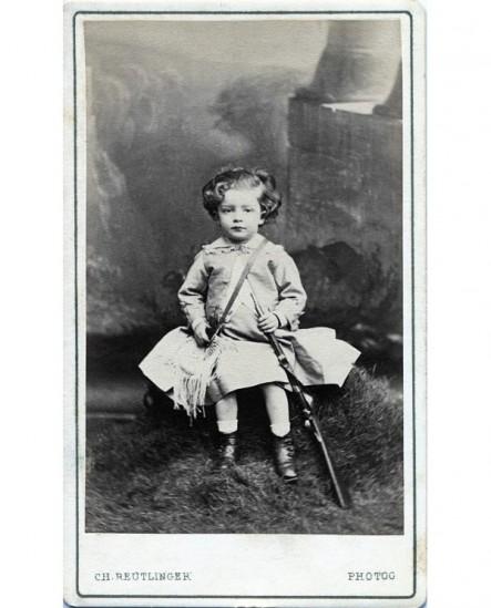 Enfant en robe avec gibessière et carabine. jouet