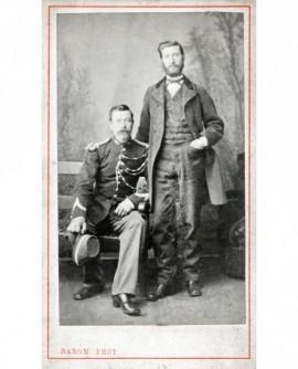 Gendarme assis, képi à la main et homme barbu debout