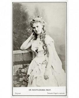 Jeune femme en robe légère, l'air romantique, appuyée sur un muret
