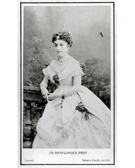 Jeune femme en robe blanche décolletée, une fleur au creux des seins
