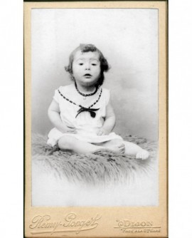 Bébé en chemise et collier à gros grains, assis sur peau de mouton