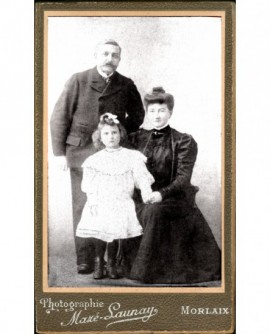 Portrait de famille: père moustachu et fillette en robe blanche debout, mère assise