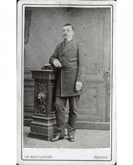 Homme moustachu debout, appuyé sur une console sculptée