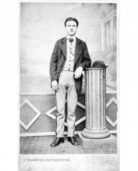 Homme pantalon à carreaux accoudé à une colonne (chapeau rond)