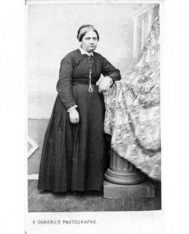 Femme en robe noire debout, accoudée à une colonne drapée