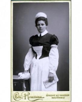 Jeune femme en tenue de servante debout, le Mémorial ségusien à la main