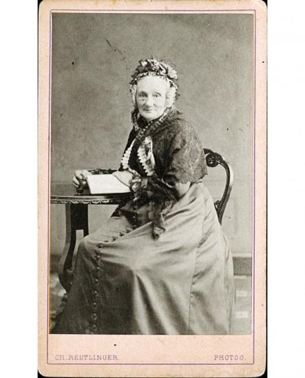 Femme âgée,en bonnet, assise à une table avec un livre ouvert