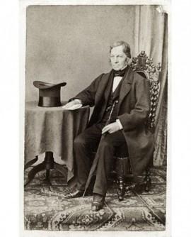 Homme assis un papier à la main, son chapeau posé sur la table