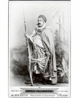 Arabe en burnou debout, un fusil à baïonnette à la main