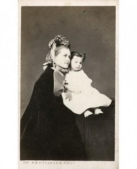 Femme en manteau et chapeau, une fillette en robe blanche dans les bras