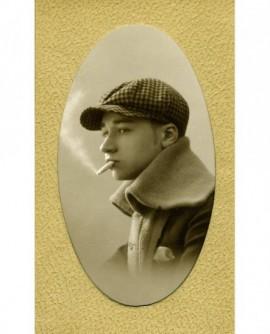 Portrait de jeune homme à casquette à carreaux une cigarette au bec