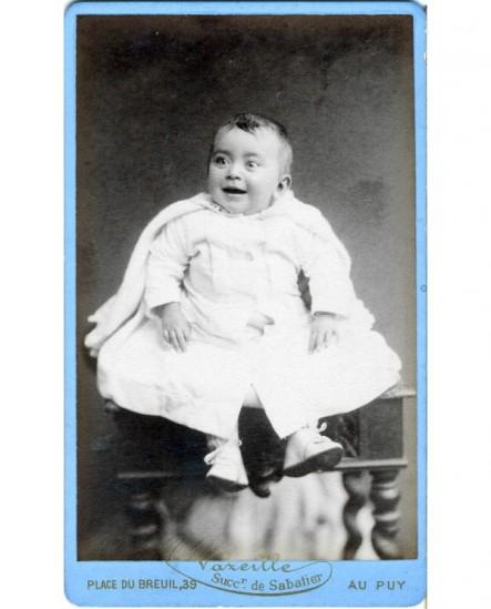 Bébé rieur en robe blanche assis