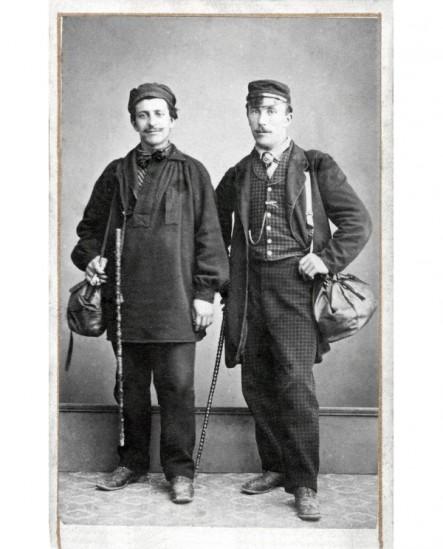 Deux hommes en casquette debout avec cannes et besaces: compagnons ?