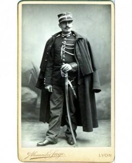 Gendarme moustachu debout en képi, pélerine sur les épaules (militaire)