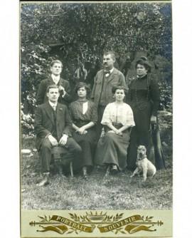 Famille dans un jardin: père, mère et les quatre enfants adolescents, plus le chien