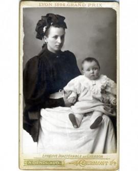 Nourrice en veste et coiffe, bébé sur genoux. Yvonne Lineyre
