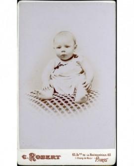 Bébé en chemise, assis sur un coussin