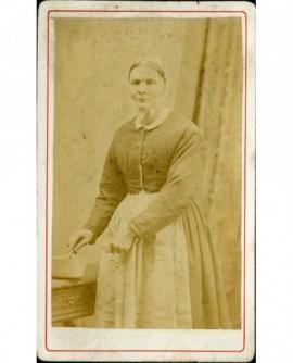 Femme en coiffe et tablier, tournant une cuillère dans une casserole