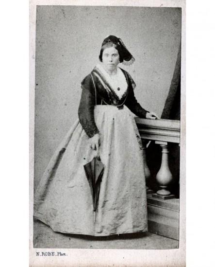 Femme en toque avec veste sur robe et ombrelle